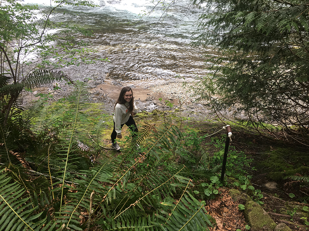 A teen exploring the shores of the Washougal River at TreeSong